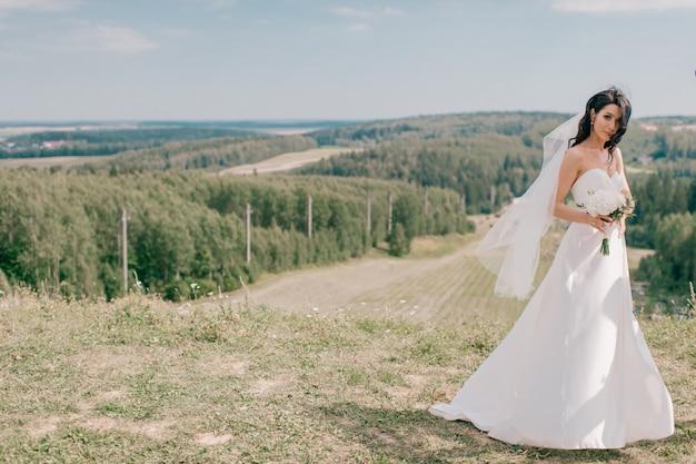 自然の丘でポーズ白いウェディングドレスの若い美しい花嫁。