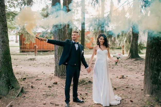 自然に一緒に立って、カラフルな煙を保持している美しい結婚式のカップル。
