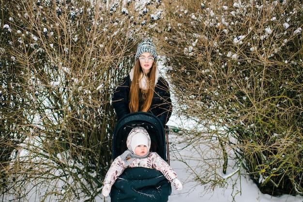 Молодая женщина с ребенком в коляске в кустах в зимний день.