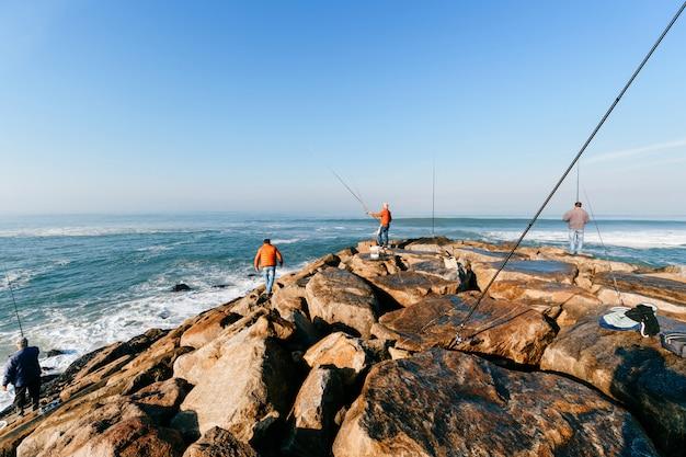 海で釣りをしている認識できない成人男性のグループ