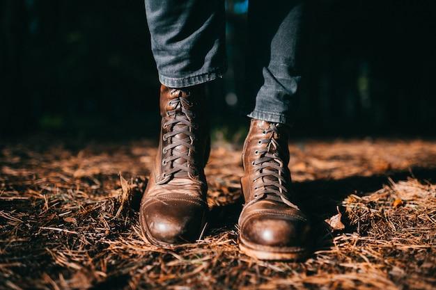 乾燥したオレンジ色のトウヒの針で地面に秋の森に立っているビンテージヒップスター男性ラフ革の木製ブーツで奇妙な木こり。