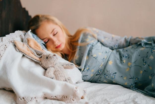ヴィンテージの木製ベッドで寝ている若い美しい金髪の十代。
