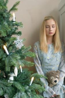 Молодая унылая девушка держа игрушку детей в комнате интерьера рождества с украшениями