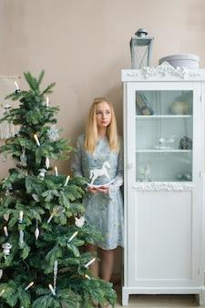 Молодая унылая девушка держа игрушку детей внутри в комнате с рождественской елкой.
