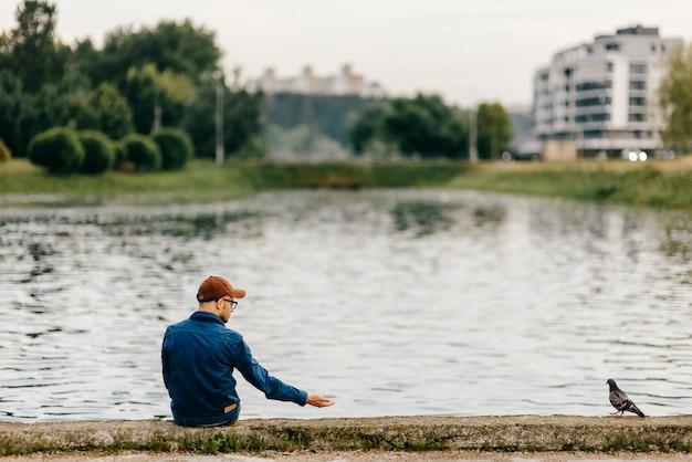 Одинокий неузнаваемый взрослый мужчина сидит на краю набережной перед озером и зовет голубя, смотрящего на него