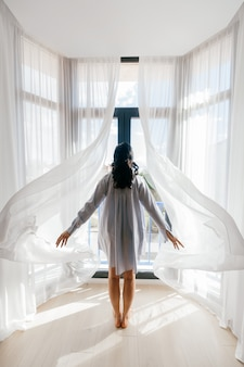 Молодая девушка стоит спиной и открывает шторы.