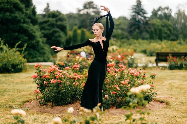 Молодая балерина в черном платье позирует и показывает балетные позы в летнем парке