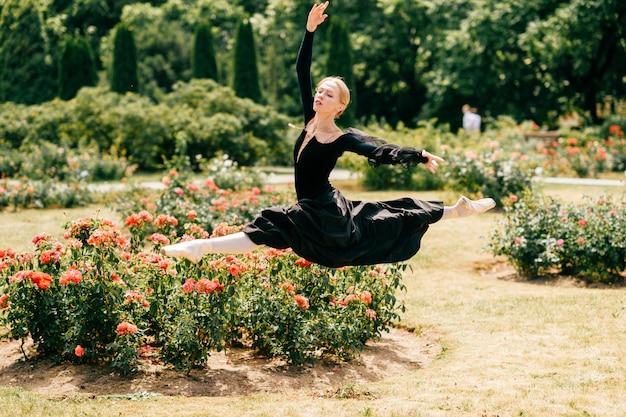 Молодая балерина в черном платье прыгает среди кустов роз в парке