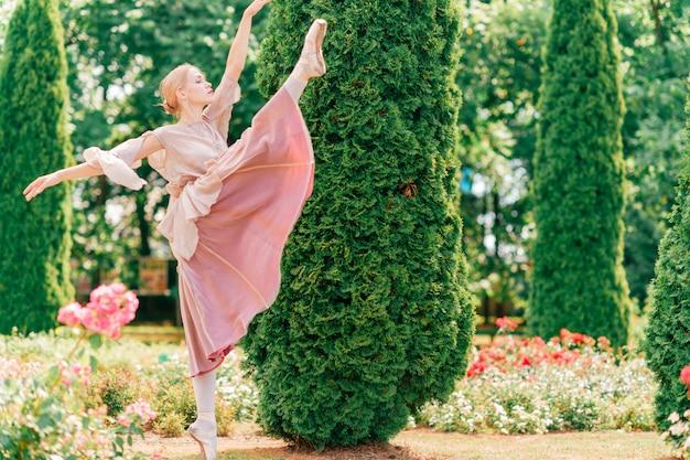 エレガントなバレリーナは、美しいイタリアの庭でバレエのポーズを示しています