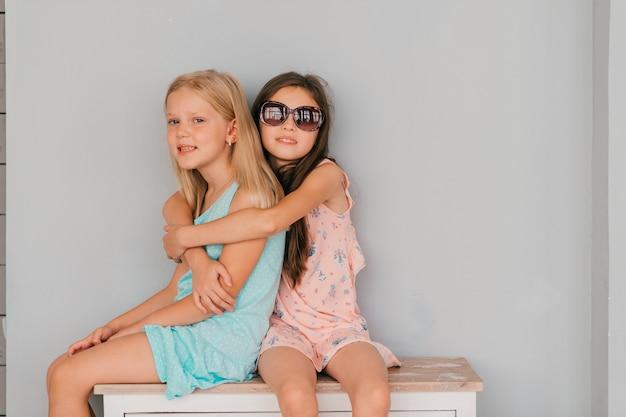 Две красивые стильные девушки обнимаются на комоде против серой стены на стене.