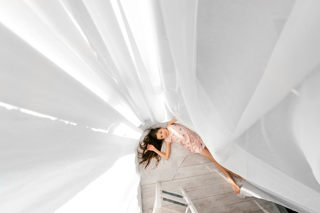 床に横たわって長い髪の美しい少女の上からの肖像画