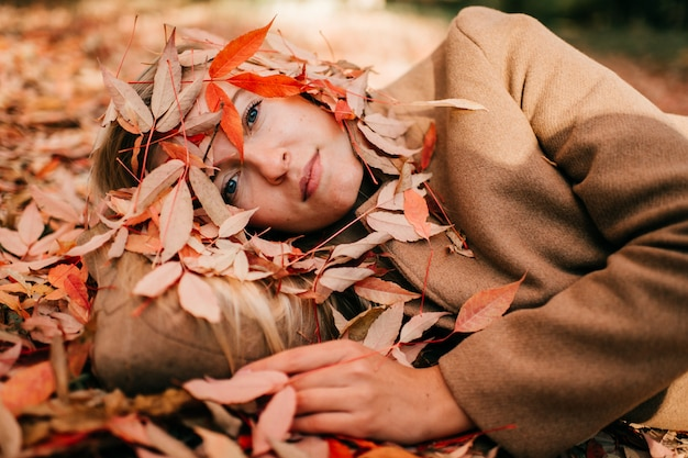 秋のうつ病。悲しいメランコリックな目で地面に横たわっているウールブラウンファッショナブルなコートの美しい少女。