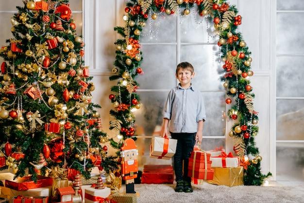 飾られたクリスマスツリーとスタジオでカメラにポーズをとって幸せな笑みを浮かべて少年