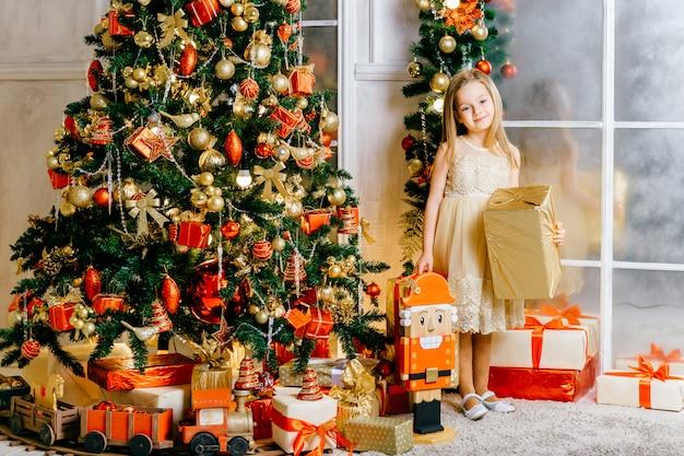 ギフト用の箱とクリスマスツリーの近くに立って、カメラにポーズをとってお祝いドレスで幸せな笑顔の女の子