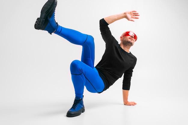 青いタイツと白いスタジオの壁を越えてストレッチと運動のブーツでスタイリッシュな男のファッションの肖像画。
