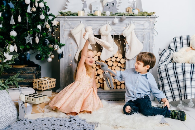 クリスマスツリーと暖炉のある部屋で遊んでいる素敵な子供たち。冬の休日の概念。