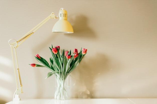 花の花束。花瓶のチューリップと家の内部の黄色のランプ