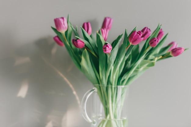 灰色の壁に美しいチューリップの花束とガラスの花瓶