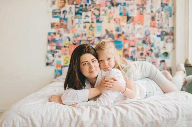 幸せなママのライフスタイルソフトフォーカスの肖像画は、白いベッドに彼女の愛らしい娘を抱擁します。