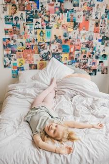 ピエロ、浮気、子供部屋の白いベッドに顔を作る面白い女の子。