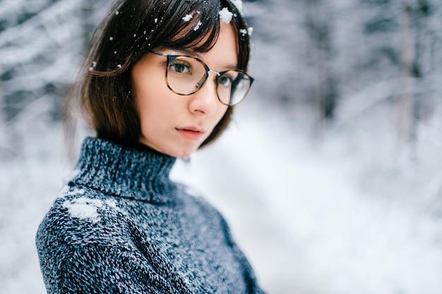 寒い冬の森で屋外ニットセーターの肖像画の若い美しい素敵な女の子。