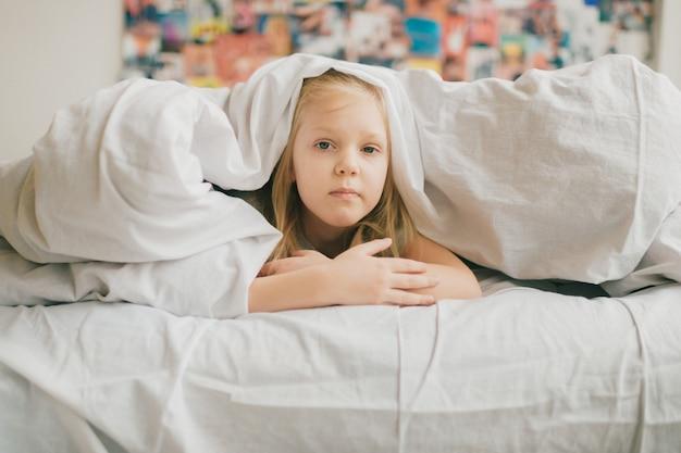 白い毛布の下のベッドに横たわって変な顔を持つ愛らしい金髪少女と悲しい目でカメラを見てください。