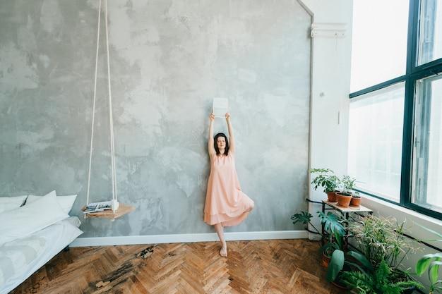 Женщина прислонилась к ноге к ноге и подняла руку с журналом в комнате во французском стиле.