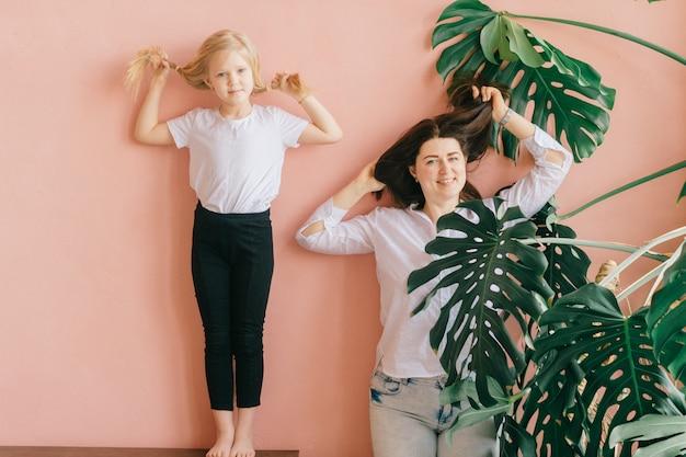 幸せな母と笑顔の娘のライフスタイル女性家族の肖像画は、ヤシの木の枝の家の壁とピンクの壁に同じポーズを作ります。同じポーズの金髪娘と陽気なママ