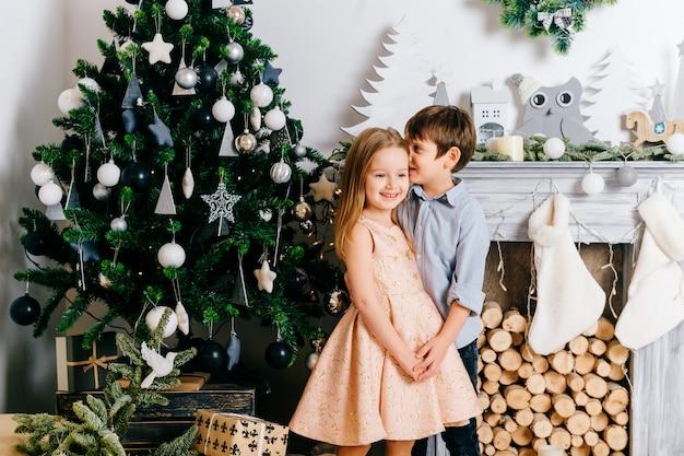 暖炉のあるクリスマスツリーのフロンで彼のキュートで美しいガールフレンドの耳にささやく微笑む少年。