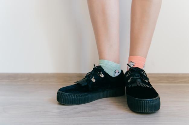 黒のエレガントなフェミニンな黒のスエードの靴の女性の足はタンケット付き。ミスマッチコットンソックスの女性の足。