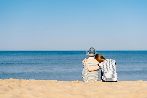 コストのビーチの砂の上に一緒に座って、海の地平線を遠く見て恋人のカップル。海で抱きしめる少女と少年。バカンス旅行。無限の美しい海の景色を楽しんでいる友人のペア