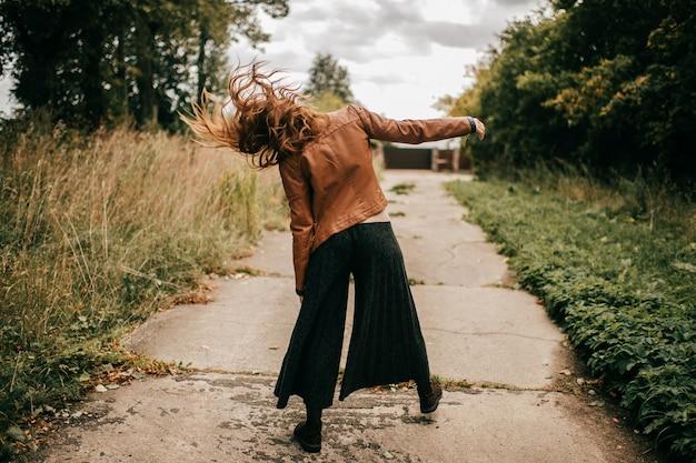 自然の道でゾンビのように歩いている奇妙なスタイリッシュな女性の後ろからの肖像画