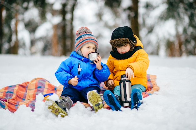 Маленькие мальчики устраивают пикник в зимнем лесу. молодые парни пьют чай из термоса в снежном лесу.