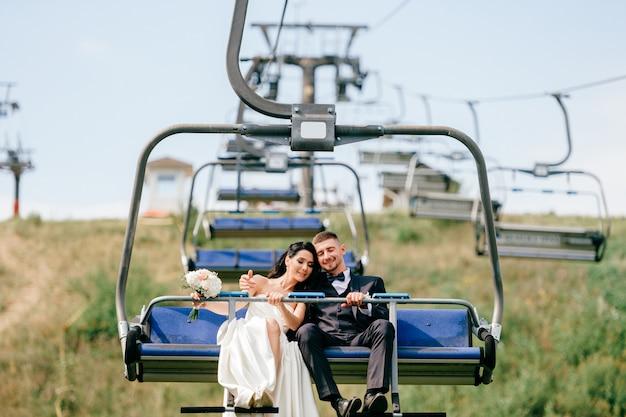 夏にケーブルカーで山から降りてちょうど結婚したカップル。索道での幸せな結婚式のペアの肖像。花嫁の日を祝う花嫁とグロム。素敵な愛情のあるペアは結婚を楽しんでいます。