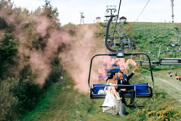 夏に山から索道に乗って幸せな結婚式のカップル。屋外のケーブルカーでキスするブライダルペア。カラフルな煙を手に保持しているハンサムな新郎と白いドレスで日焼けした花嫁。新婚。