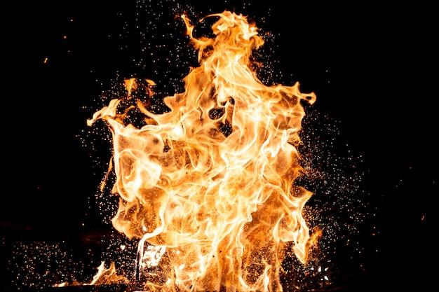 火花、炎、煙で燃える森。黒の背景に奇妙な奇妙な素朴な炎のような数字。石炭と灰。夜の抽象的な形。自然に屋外のかがり火。要素の強度