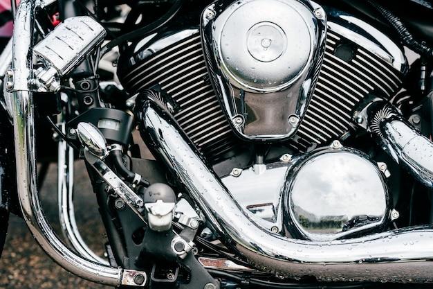 クロムの詳細がたくさんあるバイクエンジンのクローズアップ写真。エキゾーストパイプを備えた最新のパワフルなロードバイク。チョッパーモーター。