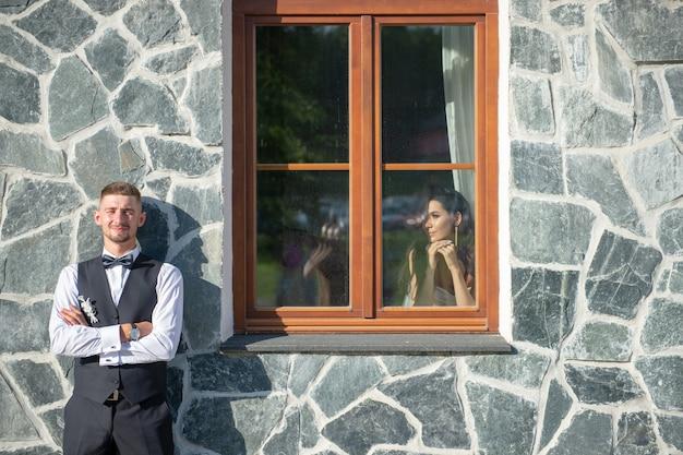 窓から彼を見ている彼の花嫁と石の壁の前に立っているエレガントな新郎。
