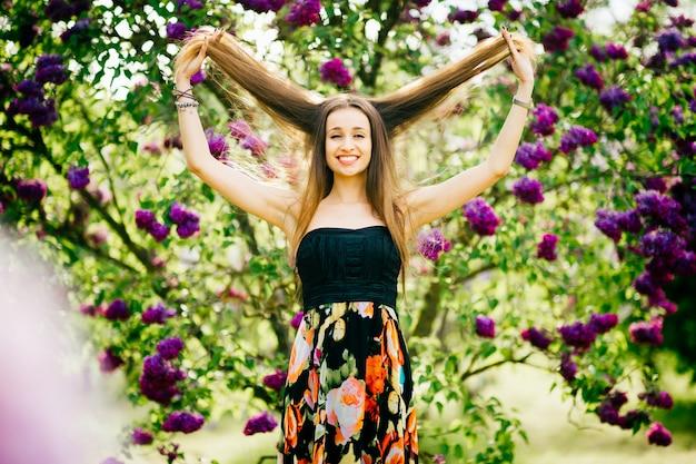 彼女の長い髪を伸ばし、咲くライラックツリーに笑みを浮かべて美しい若いブルネットの少女