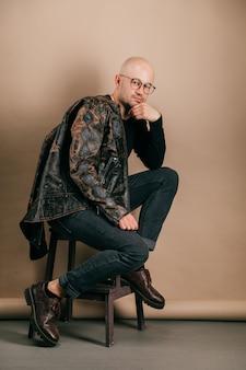 スタジオでコーヒー紙の背景にポーズのスタイリッシュな服で大人のハゲ自信を持って男の肖像。