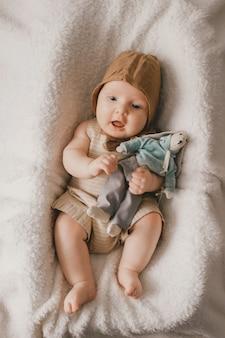 上から幸せそうな顔のライフスタイルの肖像画を笑顔で愛らしい素敵な新生児男性の赤ちゃん。白いベッドカバーで覆われたバスケットでおもちゃで横になっている面白い幼児。