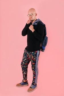 Портрет уверенно лысый мужчина в стильной одежде на розовом фоне в студии.