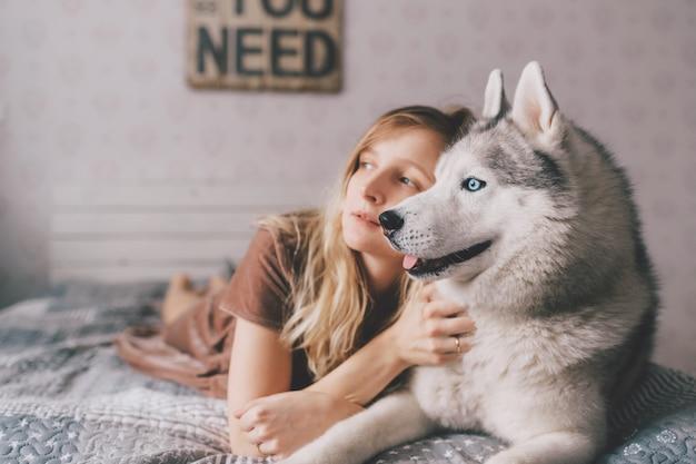 ベッドに横になっている茶色のドレスの少女とハスキーの子犬を抱擁します。美しい女性のライフスタイル屋内ポートレートは、ソファにハスキー犬を抱擁します。ペット好き。愛らしい犬と休んで陽気な女性