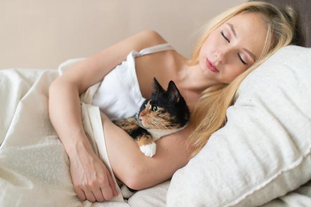 子猫と一緒に寝ている若いブロンド。