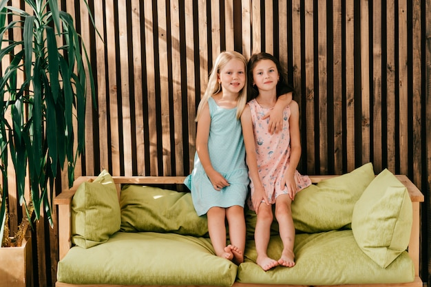 Две маленькие модельные девушки в красивых платьях сидят на лимонной кровати с деревянной стеной