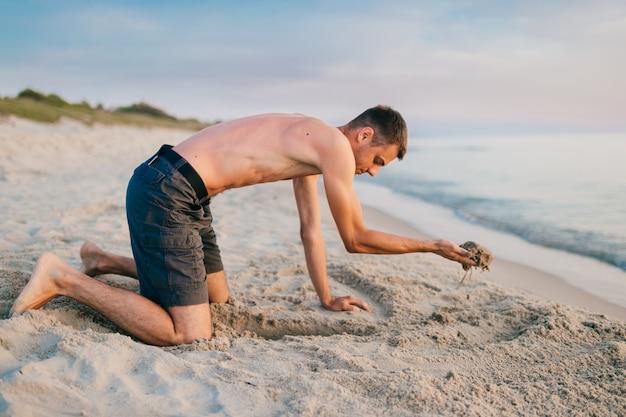 Молодой топлес босиком человек в шортах, стоя на коленях и рытье ямы руками на пляже за морем в летний вечер.