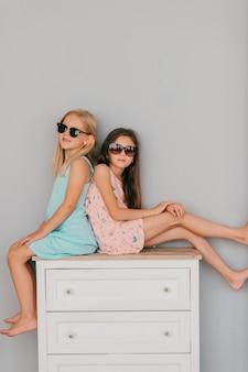 Две стильные маленькие девочки в ярких платьях и темных очках с эмоциональными лицами сидят на комоде над серой стеной