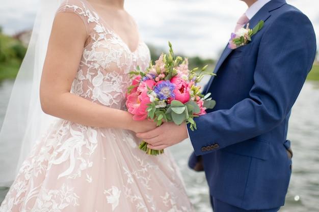 自然で写真家のためにポーズをとって、手に花を持つ認識できない結婚式のカップル