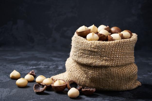 黒いテーブルの上にバッグにマカダミアナッツ。マカダミアのヒープまたはスタック。
