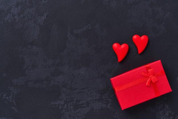 Подарочная коробка с и два красных сердца на черном фоне, вид сверху.